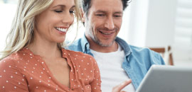 couple looking at tablet smiling.
