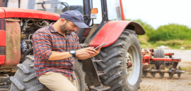 Farmer with smartphone leaning on tractor